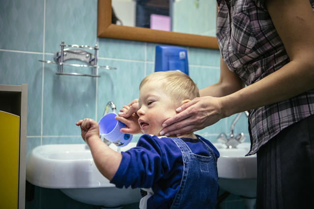 A caregiver helps a child wash his face