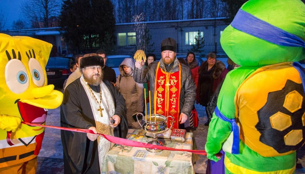 Открытие кафе в Северодвинске: священник режет ленточку, которую держат Губка Боб и Черепашка-ниндзя