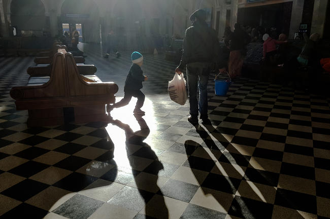 A boy from a family of refugees playing in the waiting hall at the Brest train station. This photograph was taken on November 14, 2016.