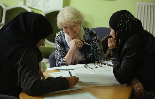 A volunteer teaching German to female refugees from Syria (on the left) and Chechnya (on the right) in a refugee center. Berlin, November 10, 2015