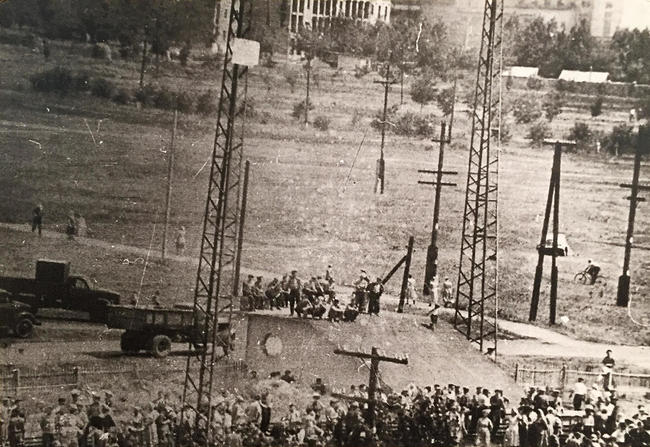 "The first day of protests: workers block the railway and hang from an electrical tower a banner reading, ""Meat, butter, and higher pay!"" June 1, 1962. Image displayed at the Novocherkassk Memorial Museum."