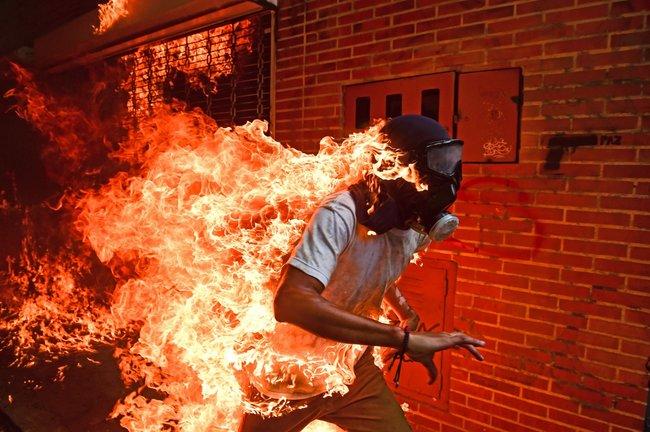 Главный приз конкурса World Press Photo 2018 получил фотограф изВенесуэлы Роналдо Шемидт заснимок охваченного огнем бегущего мужчины впротивогазе. Человек нафото— участник демонстрации против решения венесуэльского президента Николаса Мадуро внести изменения вконституцию страны. Акция протеста прошла вКаракасе 3мая 2017 года. Вэтот день врезультате столкновений протестующих сполицией встолице Венесуэлы пострадали несколько сотен человек.