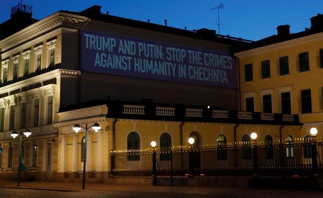 «Трамп иПутин, остановите преступления против человечности вЧечне». Проекция настене рядом спрезидентским дворцом вХельсинки, 15июля 2018 года