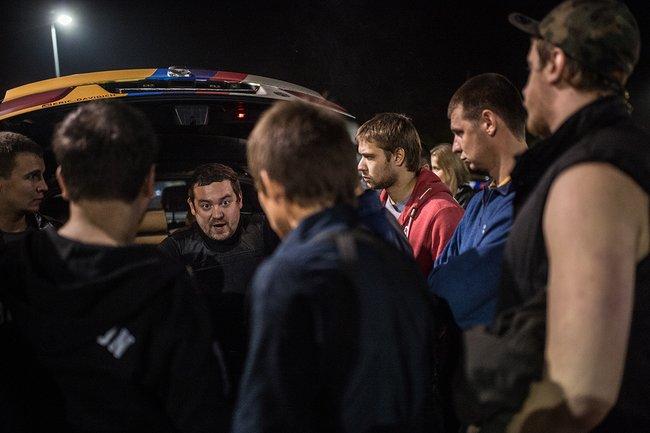 Организатор рейдов стритрейсеров Эрик «Давидыч» Китуашвили (третий слева) проводит инструктаж участников патруля, 13сентября 2014 года