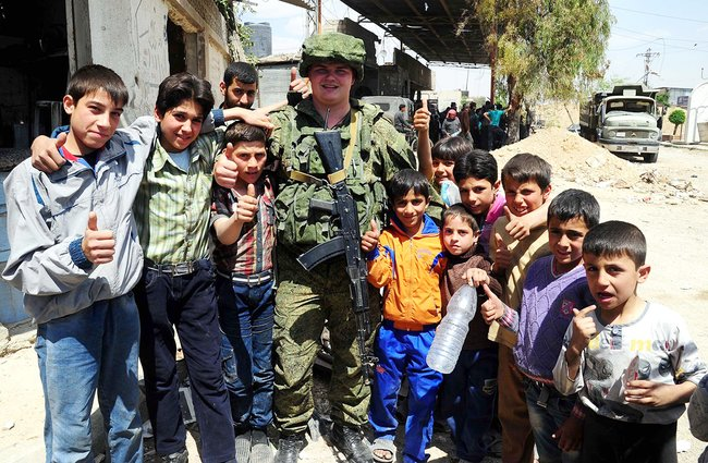 A Russian soldier surrounded by children in a suburb outside Damascus