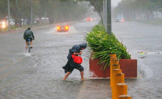 """Насевер Филиппин вночь на15сентября обрушился тайфун «Мангхут», вызвавший многочисленные разрушения. Покрайней мере два человека <a href=""""https://twitter.com/cnnbrk/status/1040886882299723776"""" target=""""_blank"""">погибли</a>. Так, посообщению правительства, вгороде Тугегарао пострадало практически каждое здание. Нафотографии— прохожие наулице вМаниле."""