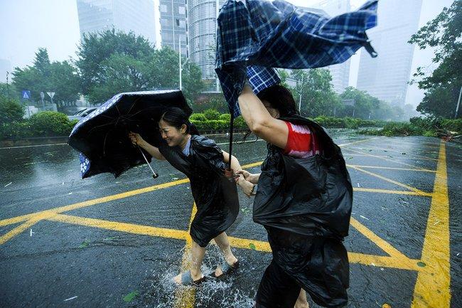 Пешеходы пытаются идти поулице против ветра вкитайском Шэньчжэне