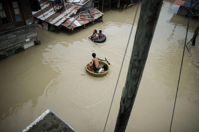Дети пересекают затопленную улицу наавтомобильных шинах икорытах вфилиппинской провинции Булакан