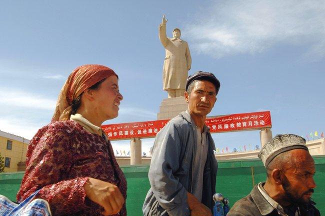 Уйгуры наНародной площади вКашгаре, где установлена 20-метровая статуя Мао Цзэдуна, 16августа 2009 года