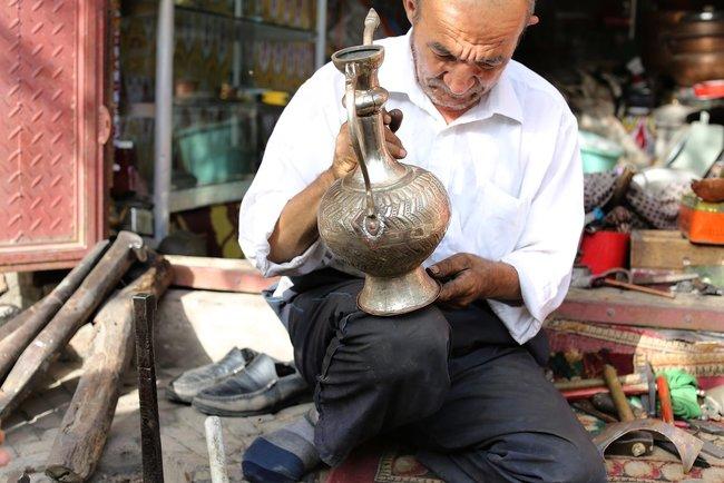 """A <a href=""""https://ru.wiktionary.org/wiki/%D0%BB%D1%83%D0%B4%D0%B8%D0%BB%D1%8C%D1%89%D0%B8%D0%BA"""" target=""""_blank"""">metal craftsman</a> at the market in Kashgar"""