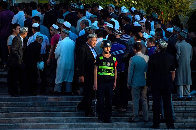 A Chinese police officer outside the central mosque of Kashgar just before the morning prayer, June 26, 2017