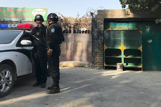 Police near the wall of a reeducation camp in Xinjiang, November 2, 2017