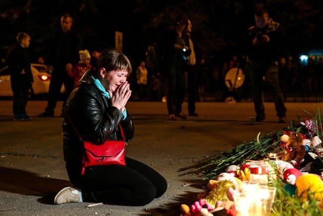 """Жители Керчи несут цветы исвечи кзданию политехнического колледжа, где 17октября произошло массовое убийство. Погибли, <a href=""""https://meduza.io/news/2018/10/18/chislo-pogibshih-pri-massovom-ubiystve-v-kerchi-vozroslo-do-20-chelovek"""" target=""""_blank"""">попоследним данным</a>, 14 учеников ипятеро сотрудников колледжа. Предполагаемый убийца, 18-летний Владислав Росляков, покончил ссобой. Более 40 человек получили ранения."""