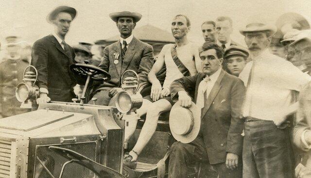 Победитель марафона вСент-Луисе Томас Хикс вокружении организаторов забега, 1904 год