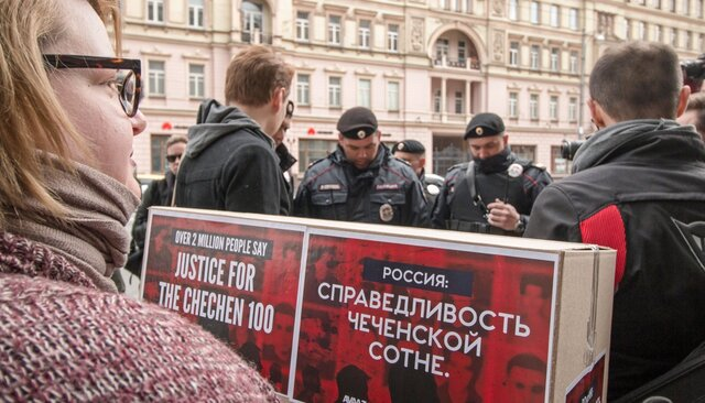 Activists carry signed petitions protesting the treatment of LGBTQ people in Chechnya to the office of Russia's Prosecutor General while police prepare to detain them. Moscow, May 11, 2017