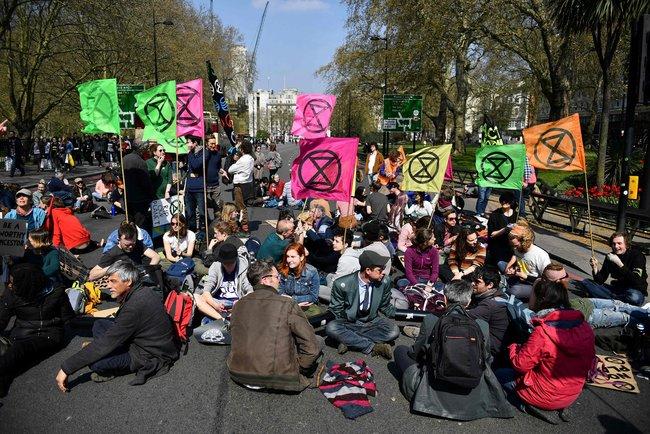 """Активисты издвижения «Восстание вымирающих» иприсоединившиеся кним днем 15апреля <a href=""""https://www.reuters.com/article/us-britain-protest-climate-change/thousands-of-activists-block-london-roads-to-demand-action-on-climate-change-idUSKCN1RR0ZI"""" target=""""_blank"""">перегородили движение</a> нанескольких улицах унаиболее известных достопримечательностей вцентре Лондона. Вакции, поданным СМИ, участвуют несколько тысяч человек. Некоторые демонстранты пришли сплакатами «Унас нет планеты Б» и«Вымирание— это навсегда». Участники акции требуют отправительства немедленно принять меры поборьбе сглобальным изменением климата. Вначале апреля активисты «Восстания вымирающих» устраивали акцию взащиту природы <a href=""""https://meduza.io/video/2019/04/02/na-galerke-u-nas-otvlekayuschiy-faktor-na-debaty-po-brekzitu-v-britanskom-parlamente-prishli-polugolye-zaschitniki-prirody"""" target=""""_blank"""">впарламенте Великобритании</a>."""