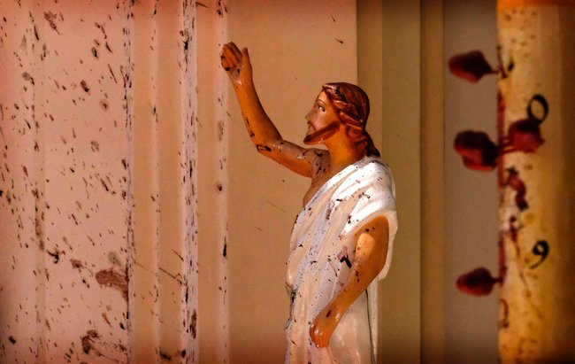 Статуя Христа вцеркви святого Себастьяна вНегомбо, пригороде столицы Шри-Ланки, где утром 21апреля произошел взрыв. Поданным полиции, его жертвами стали 104 человека. Практически одновременно совзрывом вНегомбо наШри-Ланке произошло пять других взрывов, ачерез несколько часов— ещедва. Вобщей сложности погибли более двухсот человек.