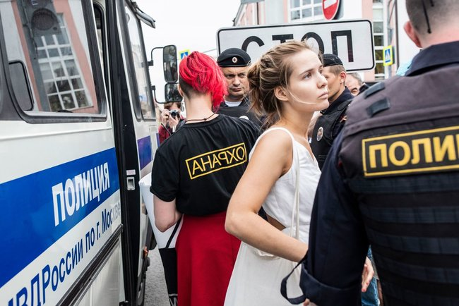 "A protester is arrested wearing a shirt that says ""anarcho,"" or ""security"" in reverse."