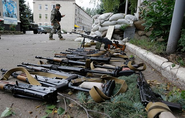 Separatist fighter walks past weapons seized from a Ukrainian military base in Donetsk, June 27, 2014
