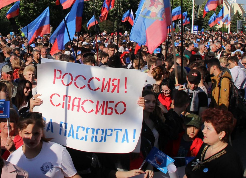 "People in Luhansk celebrate the fifth anniversary of the formation of the LNR. May 12, 2019. The march is called ""With Russia in Our Hearts,"" and the sign above reads, ""Russia, thanks for the passports!"""