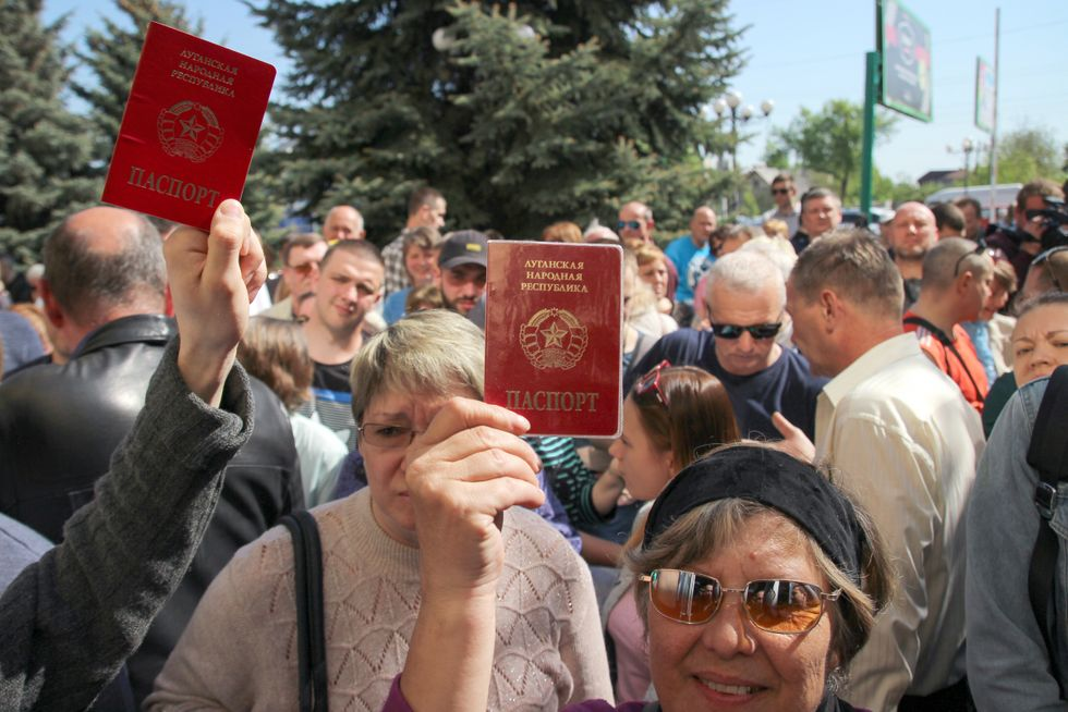 People in Luhansk hold up their passports ahead of the opening of a center where they can submit documents to obtain Russian citizenship