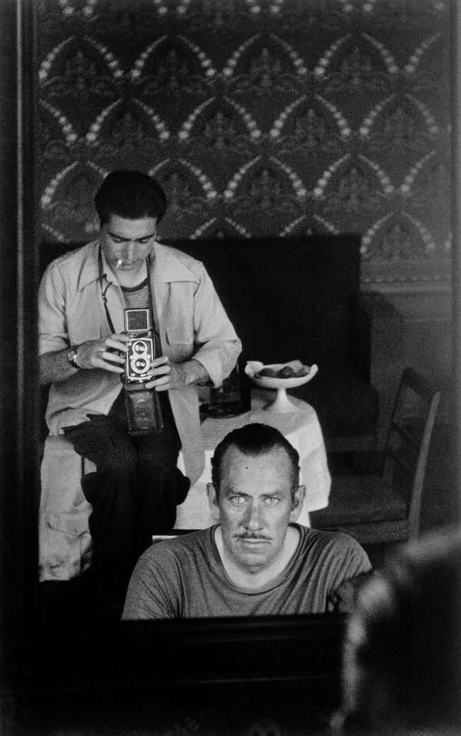 John Steinbeck and Robert Capa captured in the reflection of a mirror. USSR, September 1947.