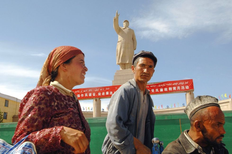 Uyghurs on People's Square in Kashgar near a twenty-meter statue of Mao Zedong, August 16, 2009
