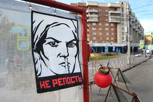 "A modified Soviet-era propaganda poster that reads ""NO REPOST"" hangs in Novosibirsk during a public art action against the prosecution of social media activity. 2018"