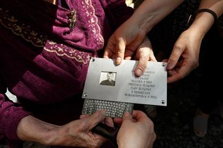 Memorial plaque for Alexey Andriyashin in the hands of his daughter, Tamara