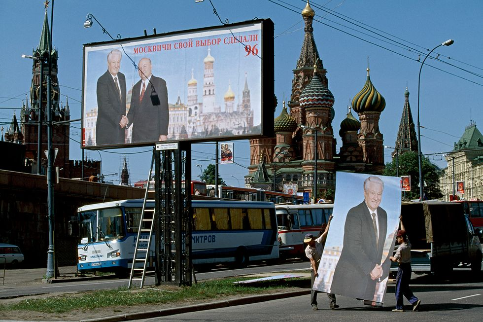 Workers put up election posters featuring Boris Yeltsin opposite Red Square. Moscow, 1996.