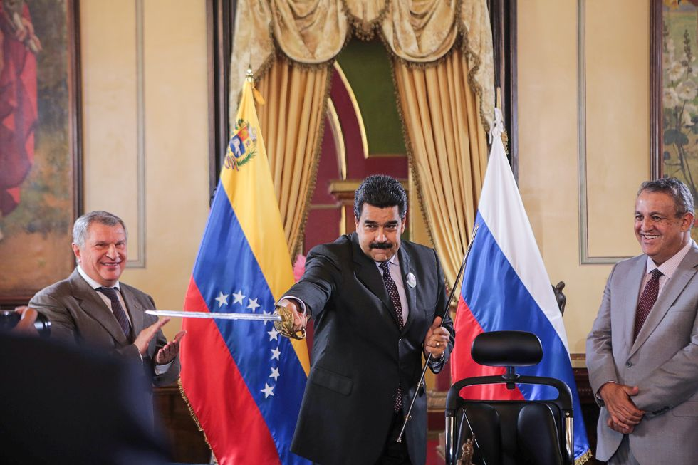 Venezuelan President Nicolás Maduro holds a replica of a sword that belonged to Venezuela's national hero, Simon Bolivar, as Rosneft head Igor Sechin and Venezuelan Oil Minister and state oil company president Eulogio del Pino look on. Caracas, Venezuela; July 28, 2016