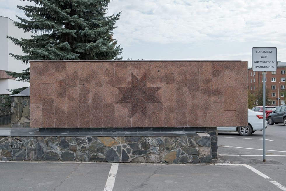 The parking lot outside Udmurtia's State Council building, which features a wall decorated with a symbol of the sun. September 2019