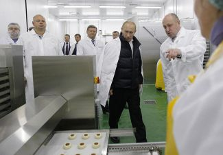 "Prime Minister Vladimir Putin during a visit to the ""Concord"" factory. Evgeny Prigozhin is standing on the right. September 20, 2010."