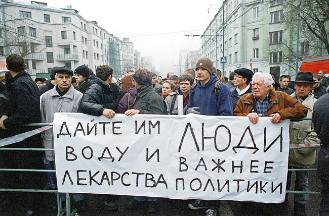"(Sign reads, ""Give them water and medicine. People are more important than politics."")"