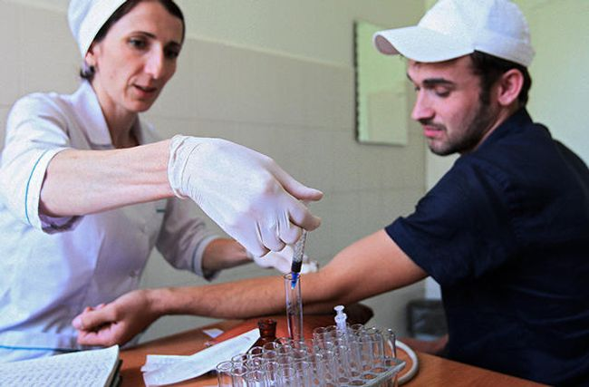 A doctor at an AIDS-prevention center takes blood from a patient to test for HIV infection. The Islamic High Council of Chechnya requires engaged couples to submit to HIV tests and requires a certificate showing a clean bill of health, in order to register a marriage.