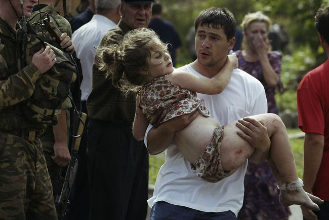 A volunteer carried a girl from the school, after the assault on the building