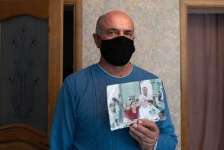 Magomed Omarov, the husband of X-ray technician Aminat Medzhidova, holds up a photo of the pair together. Medzhidova died of COVID-19 on May 2. Gergebil, Dagestan; May 27, 2020