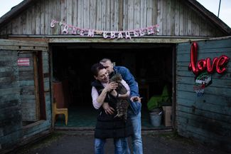 A local couple, Anna (who works as a vendor) and Sergey (a miner), celebrate their wedding outside their garage.