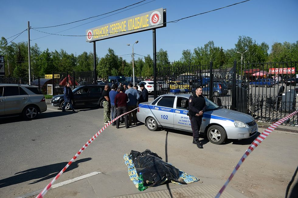 Police officer outside Moscow's Khovanskoye Cemetery, following a deadly shootout, May 14, 2016