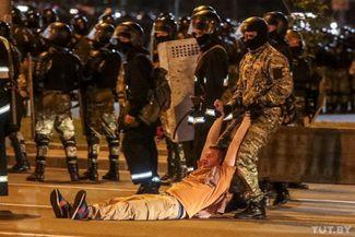 Силовик тащит мужчину по земле во время протестной акции после закрытия избирательных участков. 9 августа 2020 года