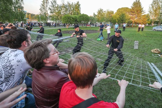 Protesters pull down a fence surrounding the construction site of St. Catherine's Cathedral in Yekaterinburg, May 13, 2019